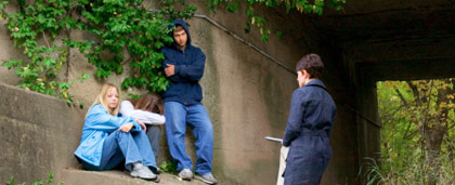 social worker speaking with young people under a bridge